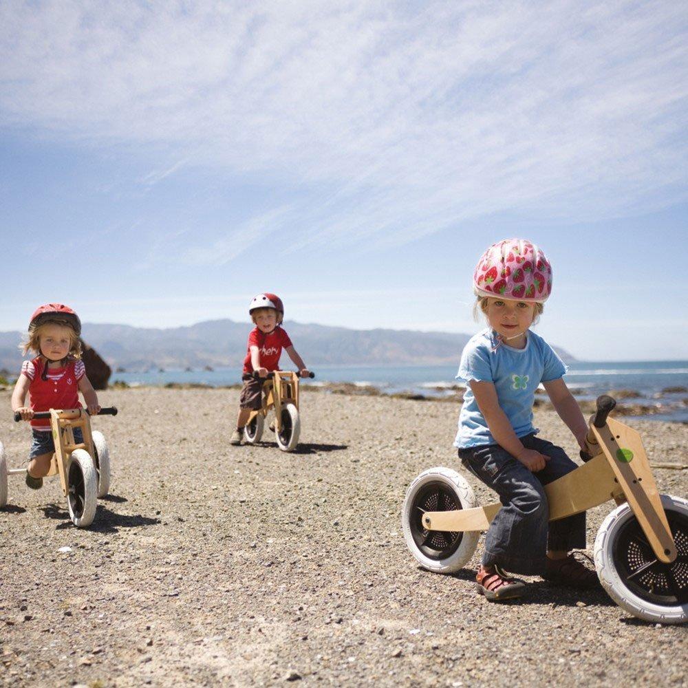 Drei Kinder mit Kinderdreirad aus Holz auf einer Straße